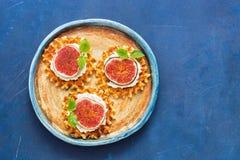 与奶油、无花果和薄荷叶的传统比利时华夫饼干在蓝色土气背景 顶视图,拷贝空间 免版税库存图片