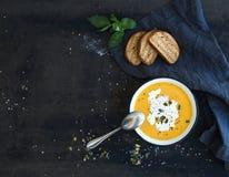 与奶油、种子,面包和新鲜的南瓜汤 库存图片
