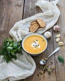 与奶油、种子,面包和新鲜的南瓜汤 库存照片