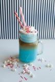 与奶油、蛋白软糖和五颜六色的装饰的蓝色咖啡在黑白背景 奶昔 免版税库存图片