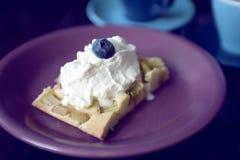 与奶油和一个蓝莓的大黄蛋糕在上面 库存图片