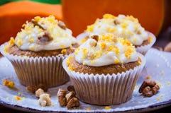 与奶油和南瓜的南瓜杯形蛋糕 免版税库存照片