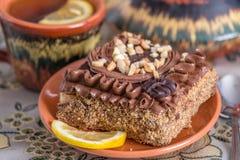 与奶油和坚果的可口和甜巧克力蛋糕和Ñ 红茶用柠檬 与茶壶、茶碟和Ñ 的茶具 库存照片