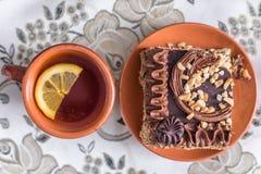 与奶油和坚果的可口和甜巧克力蛋糕和Ñ 红茶用柠檬 与茶壶、茶碟和Ñ 的茶具 免版税库存照片