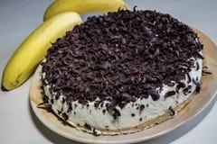 与奶油和巧克力削片的香蕉蛋糕 库存图片