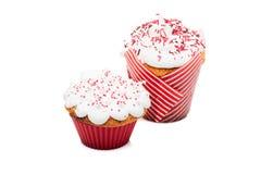 与奶油和红色结冰的两个杯形蛋糕松饼被隔绝在白色 免版税库存照片