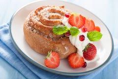 与奶油和草莓的甜桂皮卷早餐 免版税库存照片