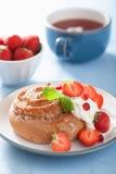 与奶油和草莓的甜桂皮卷早餐 免版税库存图片