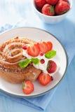 与奶油和草莓的甜桂皮卷早餐 图库摄影