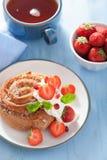与奶油和草莓的甜桂皮卷早餐 免版税图库摄影