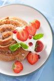 与奶油和草莓的甜桂皮卷早餐 库存照片