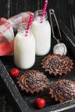与奶油和草莓,在瓶的牛奶的巧克力杯形蛋糕在一个黑木盘子 选择聚焦 免版税库存照片