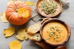 与奶油和荷兰芹的南瓜和红萝卜汤在黑暗的木ba 库存照片