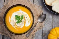 与奶油和荷兰芹的南瓜汤在木背景 图库摄影