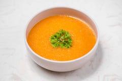 与奶油和荷兰芹的红萝卜汤在白色石背景  库存照片