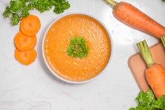 与奶油和荷兰芹的红萝卜汤在白色石背景  免版税库存图片