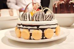 与奶油和macaron的美丽的蛋糕 免版税库存图片