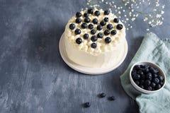 与奶油奶酪的自创蓝莓蛋糕和在黑暗的背景的新berrries r 免版税库存照片