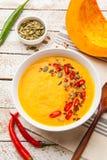 与奶油的南瓜在白色碗的汤和调味料在土气wo 免版税库存图片