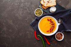 与奶油的南瓜在白色碗的汤和调味料在黑色求爱 免版税库存照片