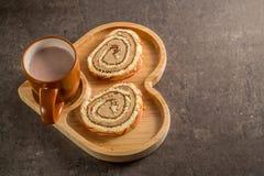 与奶油的小甜面包用在一个木心形的盘子的热的牛奶巧克力 库存图片
