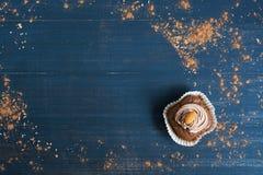 与奶油的巧克力杯形蛋糕在蓝色木背景 库存图片