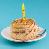 与奶油的巧克力蛋糕和在蓝色背景的一个蜡烛 库存图片