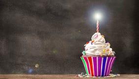 与奶油的杯形蛋糕和蜡烛有黑板背景 免版税库存照片