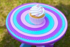 与奶油的杯形蛋糕在五颜六色的桌上 免版税库存图片