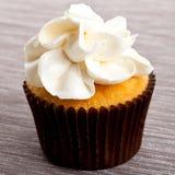 与奶油的鲜美甜自创杯形蛋糕在桌上 免版税库存图片