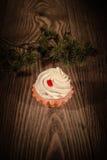 与奶油的1个蛋糕和冷杉在木背景分支 免版税库存照片