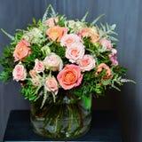 与奶油色和桃红色玫瑰的花束在一个玻璃花瓶 免版税图库摄影
