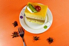 与奶油色层的鲜美黄色和棕色蛋糕。 免版税库存照片