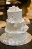 与奶油色玫瑰和装饰的三层的婚宴喜饼 免版税图库摄影
