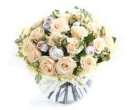 与奶油色玫瑰和贝壳,一个透明玻璃花瓶的花的布置。隔绝在白色背景。花卉构成。 库存照片