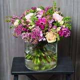 与奶油色玫瑰和紫色花的花束在一个玻璃花瓶 库存照片