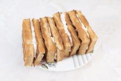 与奶油色装填的维也纳奶蛋烘饼在有一个花卉样式的一个白色茶碟 免版税图库摄影