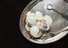 与奶油色结冰和糖粉末的桂皮卷在金属盘 免版税库存图片