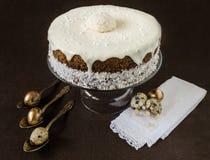 与奶油色结冰的复活节蛋糕在鹌鹑蛋和花附近 免版税库存照片