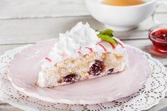 与奶油色mascarpone的鲜美在板材的蛋糕和樱桃,在轻的木背景 免版税库存图片