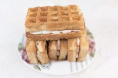 与奶油装填和一个薄酥饼的三个维也纳奶蛋烘饼在上面在一个白色茶碟说谎 库存图片