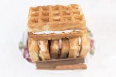 与奶油装填和桂香谎言一根棍子的维也纳奶蛋烘饼在一个白色茶碟的有在defocus的一个花卉样式的 免版税图库摄影
