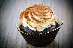 与奶油,在伍迪背景的杯形蛋糕的蛋糕 图库摄影