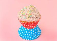 与奶油,在桃红色背景的杯形蛋糕的蛋糕 免版税图库摄影
