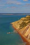 与她普遍的色的沙子的白矾海湾与码头和驾空滑车驻地 免版税库存照片