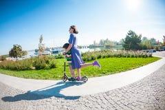 与她的儿子的妇女骑马滑行车的 免版税库存照片