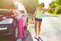 与她的十几岁的女儿的妇女司机乡下公路的,在残破的汽车附近 库存照片