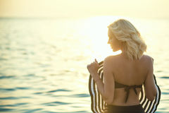 与她的华美的白肤金发的身分回到在海水的照相机在拿着在她前面的日出一个大宽充满的帽子 免版税库存图片