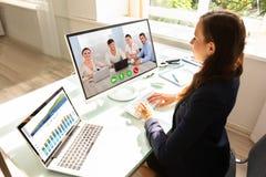 与她的同事的女实业家电视电话会议在计算机上 免版税库存图片