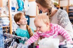与她的女儿和小儿子的母亲购物 库存图片